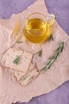 Pain croustillant au sel, pichet d'huile et brins de romarin sur papier froissé et table en bois de couleur
