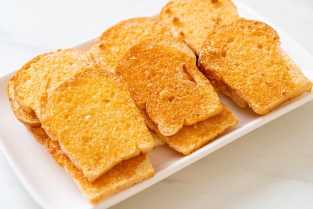 Pain croustillant cuit au four avec du beurre et du sucre sur une assiette