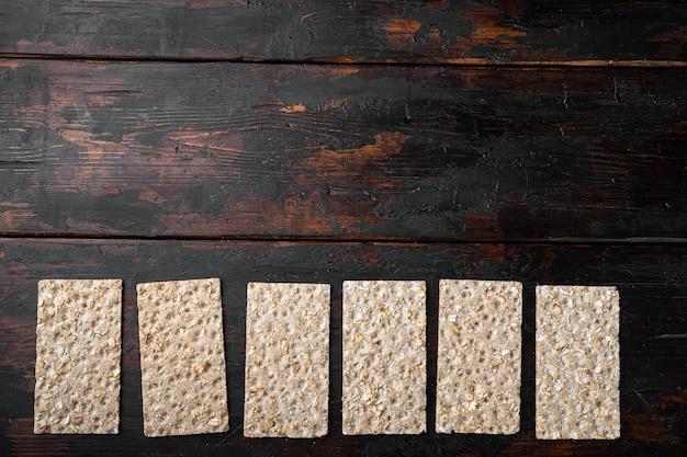 Pain croustillant avec ensemble de graines de tournesol, de chia et de sésame, sur un vieux fond de table en bois sombre, vue de dessus à plat, avec espace de copie pour le texte