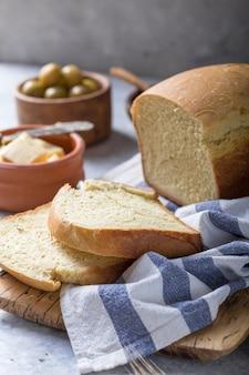 Pain croustillant fait maison avec de l'huile d'olive, du beurre et des olives vertes, vue de dessus. cuisson