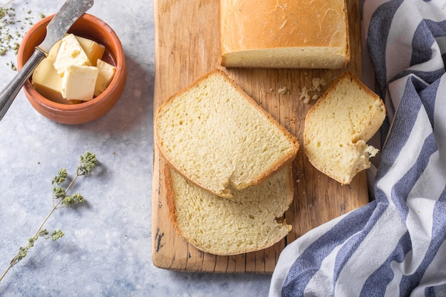 Pain croustillant fait maison et tranches avec de l'huile d'olive, du beurre et des olives vertes, vue de dessus. cuisson
