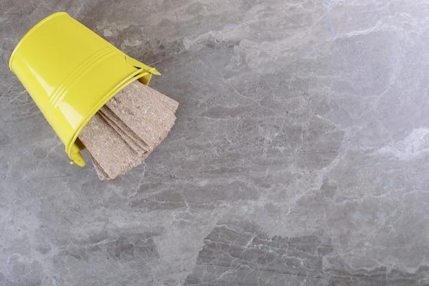 Pain croustillant tombant d'un seau jaune renversé, sur la surface en marbre