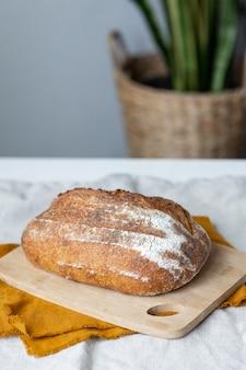 Le pain avec une croûte croustillante est beau et un délicieux pain appétissant se trouve sur une planche à découper en bois