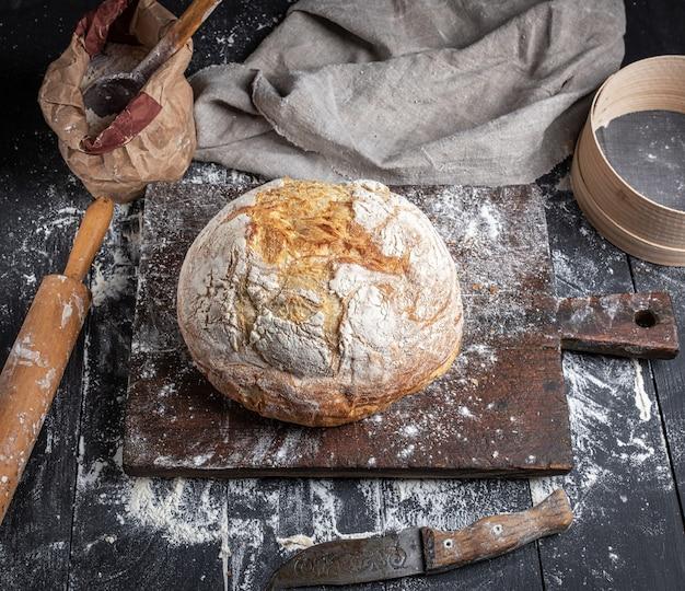 Pain cuit au four, farine de blé blanche, rouleau à pâtisserie en bois et vieille planche à découper