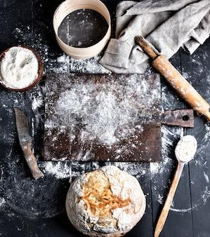 Pain cuit au four, farine de blé blanche, rouleau à pâtisserie en bois