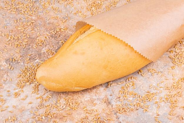 Pain dans un sac en papier à côté de grains de blé saupoudrés, sur la table en marbre.