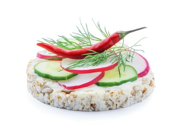 Pain diététique avec des tranches de tomate concombre radis, poivron rouge et fromage fondu sur fond blanc