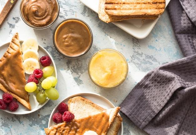 Pain doré au beurre d'amande et aux fruits. faire griller du pain avec une variété de beurre de noix. pain grillé fait maison avec de la confiture et du beurre d'arachide sur table en bois pour le petit déjeuner.