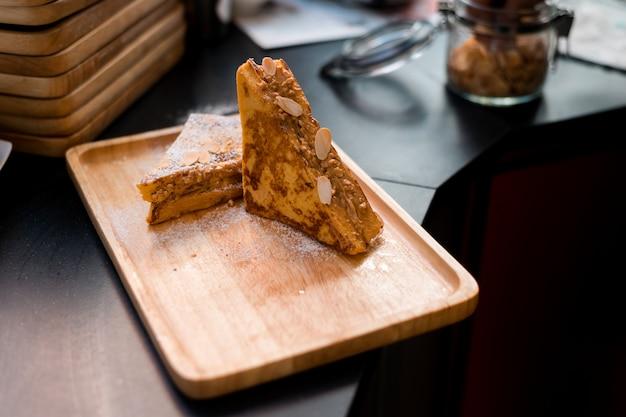 Pain doré au beurre de cacahuète sur plat en bois