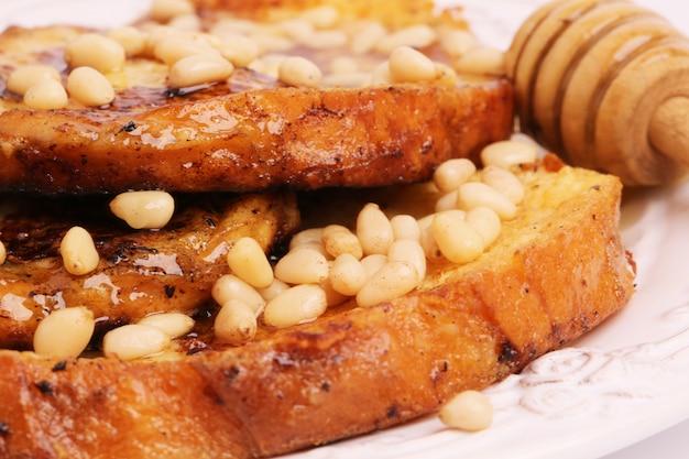 Pain doré aux croûtons au sirop de miel pignons de pin petit déjeuner dessert sucré mise au point sélective