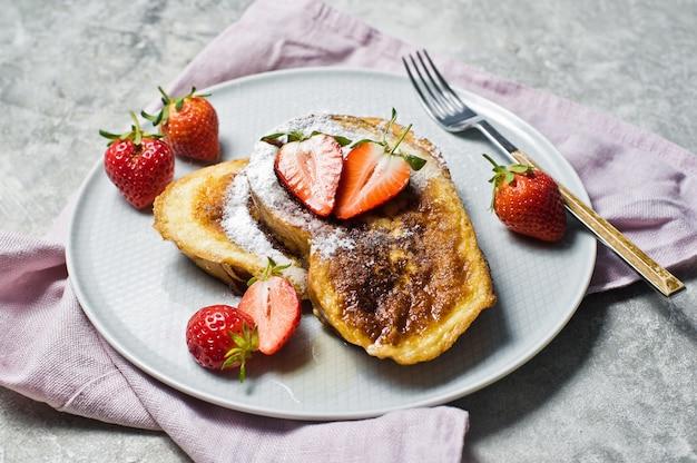 Pain doré aux fraises et au sirop d'érable sur une assiette grise.