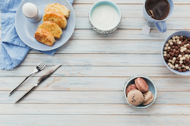 Pain doré frit avec du thé, des œufs durs et du yaourt frais. savoureux petit-déjeuner fermier. mise à plat