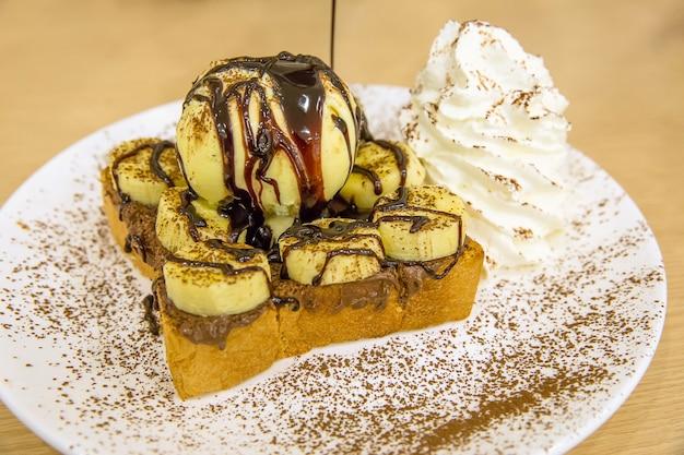 Pain doré nutella banane avec glace, saupoudrer de cacao en poudre.