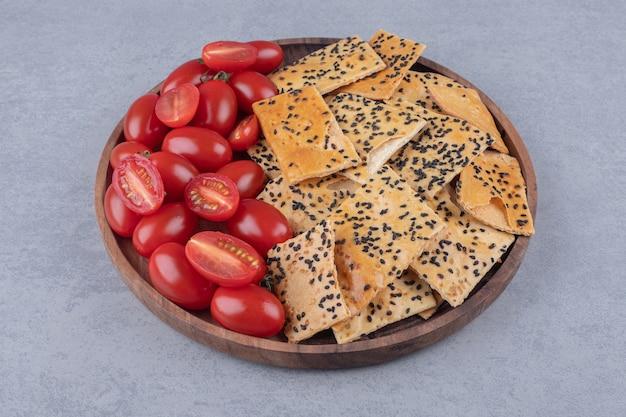 Pain enrobé de sésame et tranches de tomates empilées sur un plateau en bois sur une table en marbre.