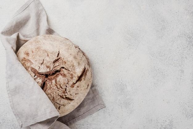 Pain entier minimaliste enveloppé dans un tissu blanc