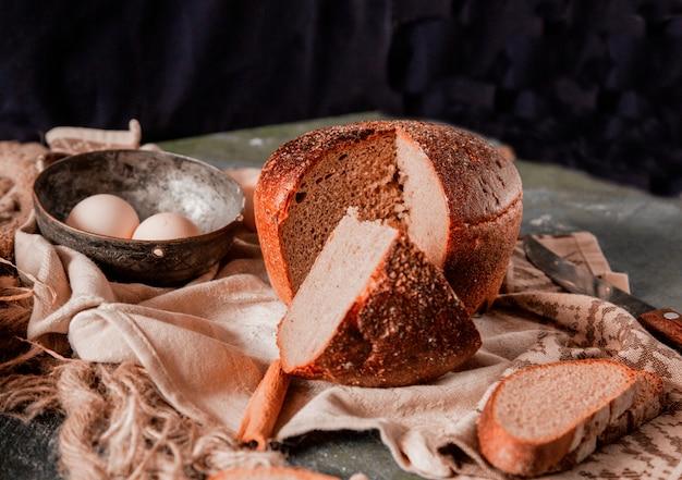 Pain entier rond et en tranches sur une table de cuisine en pierre avec des œufs et un couteau.