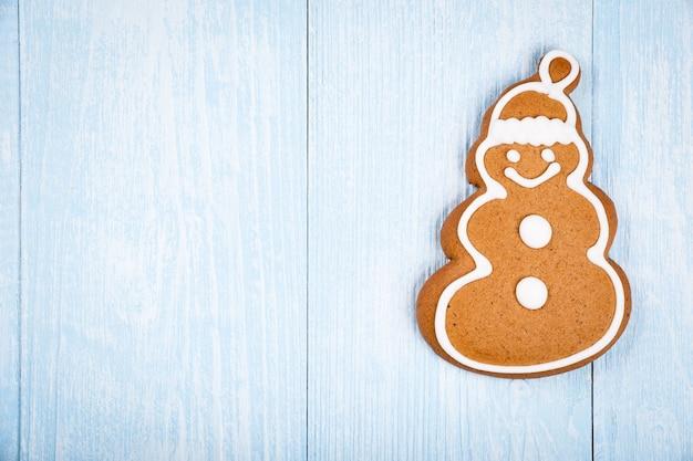 Pain d'épice de biscuit en forme de bonhomme de neige de noël sur le fond en bois bleu