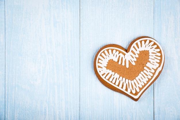 Pain d'épice de biscuit en forme de coeur de noël sur le fond en bois bleu