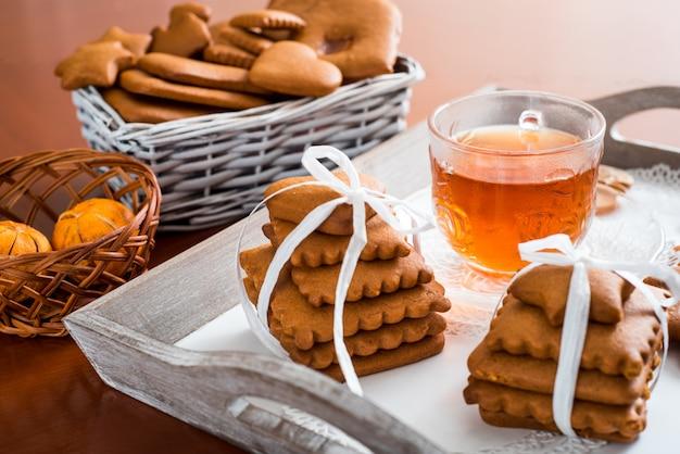Pain d'épice avec du thé chaud sur un plateau. un grand ensemble de biscuits au gingembre sur une table en bois