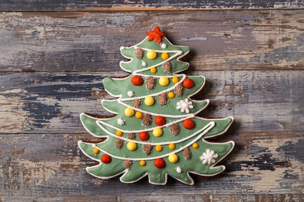 Pain d'épice de noël et du nouvel an en forme de sapin sur fond en bois bleu, pose à plat.