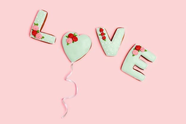 Pain d'épice peint en forme de mot amour, coeur comme ballon avec ruban sur fond rose. amour concept de romance. carte postale ou carte de voeux.
