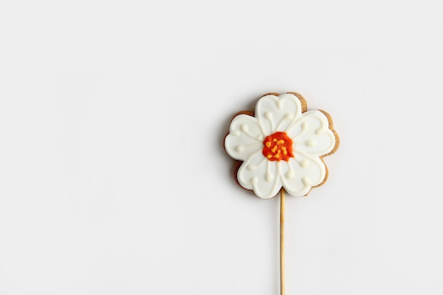 Pain d'épice sous la forme d'une fleur sur un bâton en bois isoler sur fond blanc