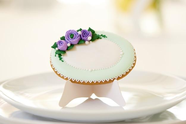 Pain d'épices rond, recouvert de glaçure blanche et décoré de fleurs violettes et de motifs sur les assiettes, près d'un verres à vin sur une table de mariage festive. la photo a été prise