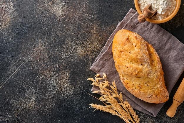 Pain fait maison avec des graines sur un support en bois, de la farine de blé et des épis sur une vieille table de fond en béton brun