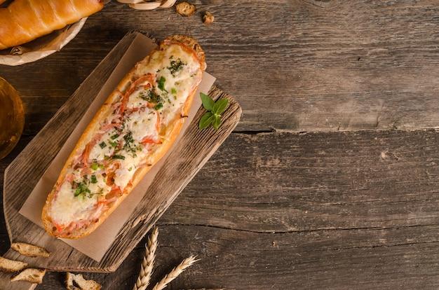 Pain farci de fromage et de tomates sur un fond en bois avec des ingrédients avec copie espace
