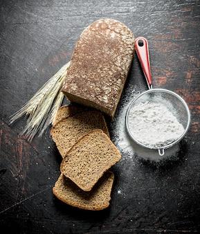 Pain avec de la farine dans une passoire et des épillets. sur rustique foncé