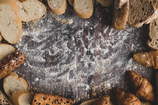 Pain et farine à pâtisserie sur une table en bois