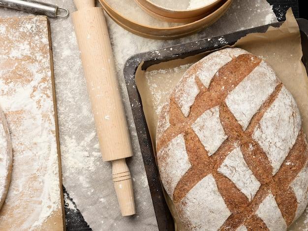 Pain de farine de seigle ovale cuit au four dans une plaque à pâtisserie en métal sur la table, vue du dessus