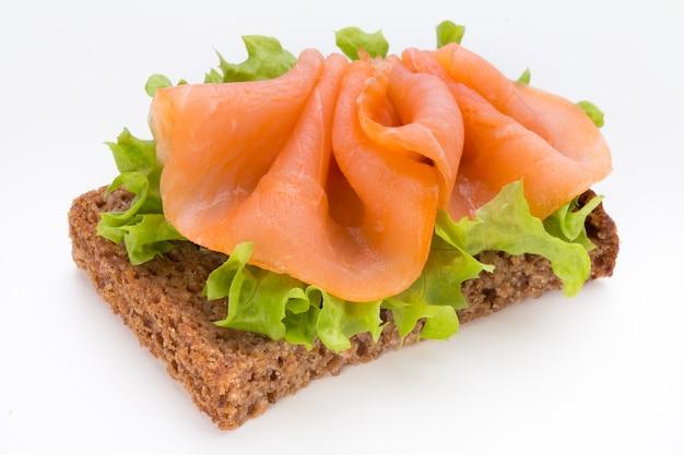 Pain avec filet de saumon frais isolé sur une surface blanche, vue du dessus.