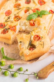 Pain focaccia italien traditionnel avec tomates et romarin dans une plaque à pâtisserie mentale
