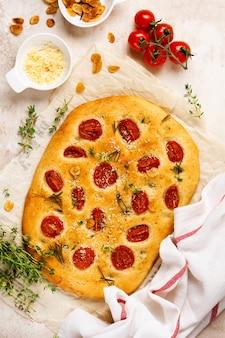 Pain focaccia traditionnel italien avec des tomates cerises, du parmesan et du romarin sur fond marron clair. vue de dessus.