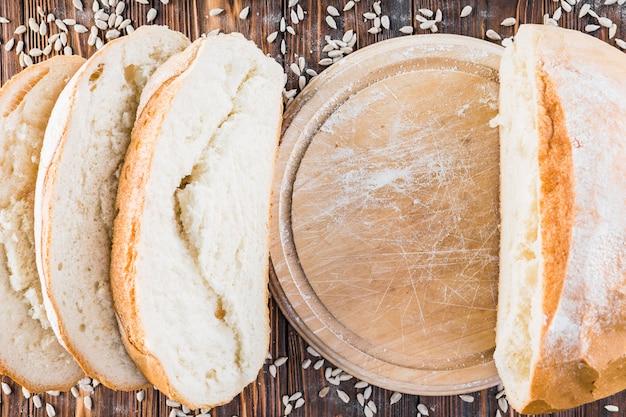 Pain fraîchement cuit et graines de tournesol sur le fond en bois