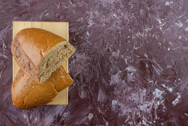 Pain frais brun haché sur une planche de bois.