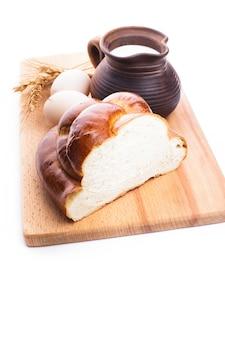 Pain frais de challah avec du lait et des œufs sur la planche de bois