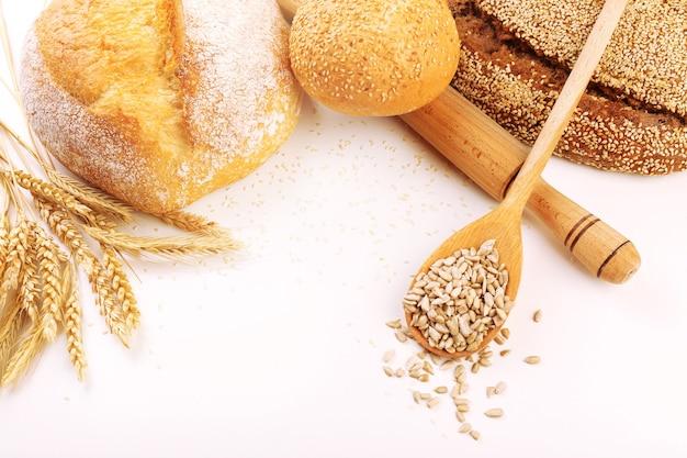 Pain frais avec du blé et une cuillère en bois de graines de tournesol sur blanc
