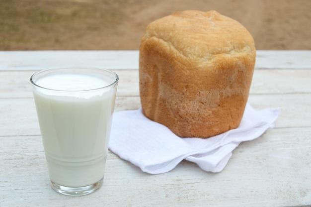 Pain frais fait maison et un verre de yaourt biologique fait maison naturel sur un fond en bois blanc