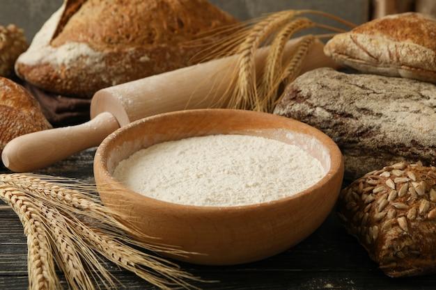 Pain frais, farine, épillets et rouleau à pâtisserie sur fond de bois