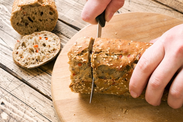 Le pain frais avec des graines de tournesol, des graines de sésame et du lin est coupé en morceaux sur une planche à découper.