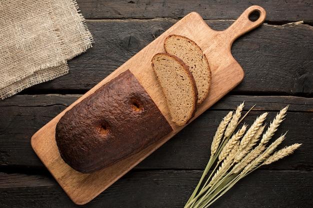 Pain frais sur une planche avec du blé sur bois