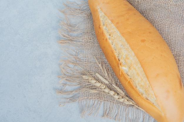 Pain frais sur toile de jute avec du blé. photo de haute qualité