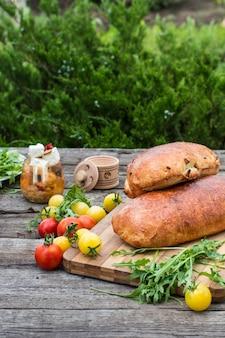 Pain frais. tomates à la roquette. feta. pique-nique, dîner en plein air. tomate jaune ve