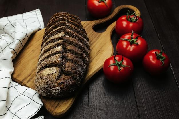 Pain frais et tomates sur table en bois. photo de haute qualité