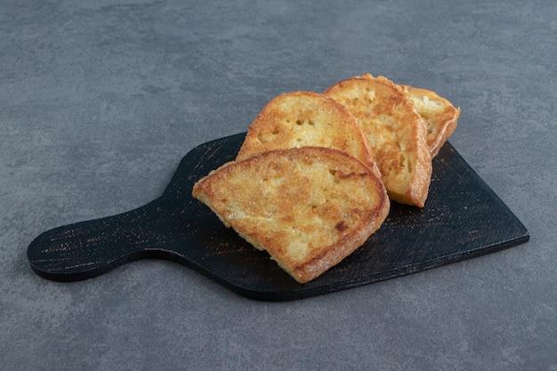 Pain frit savoureux avec oeuf sur tableau noir