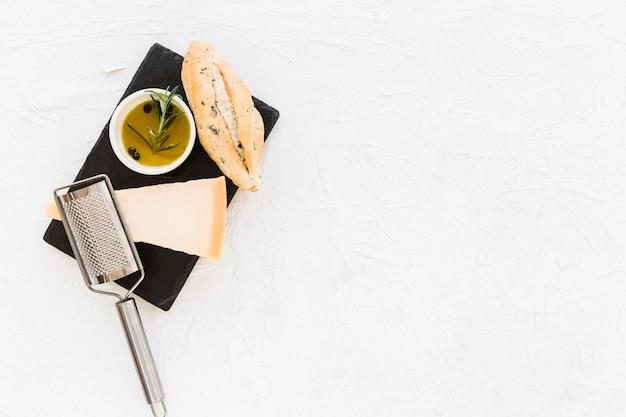 Pain avec fromage cheddar triangulaire et huile d'olive sur plaque de pierre