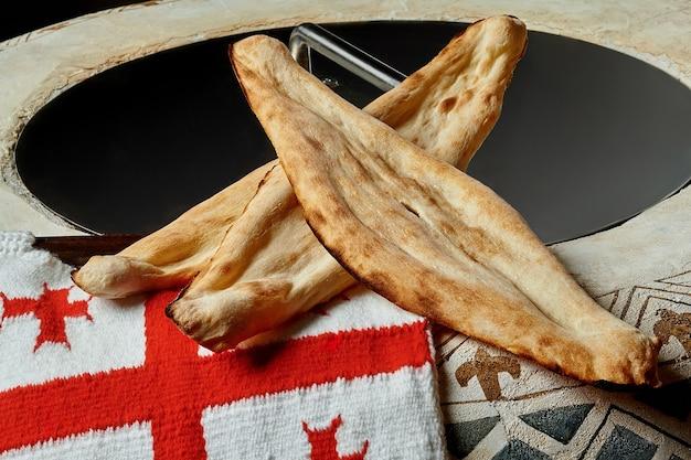 Pain géorgien traditionnel shotis puri avec drapeau national sur le four ton
