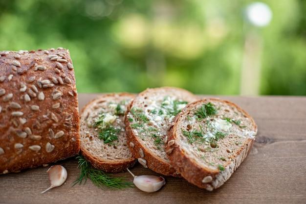 Pain de grains entiers avec des graines coupées en morceaux. toasts au beurre, aneth et ail dans la nature sur un fond en bois brun.